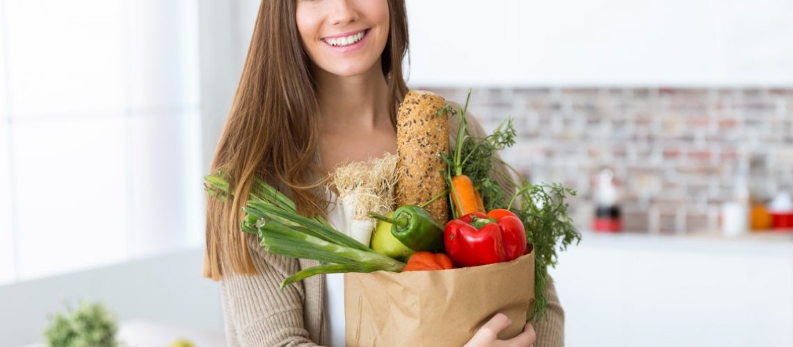 Portrait of beautiful young woman with vegetables in grocery bag at home.